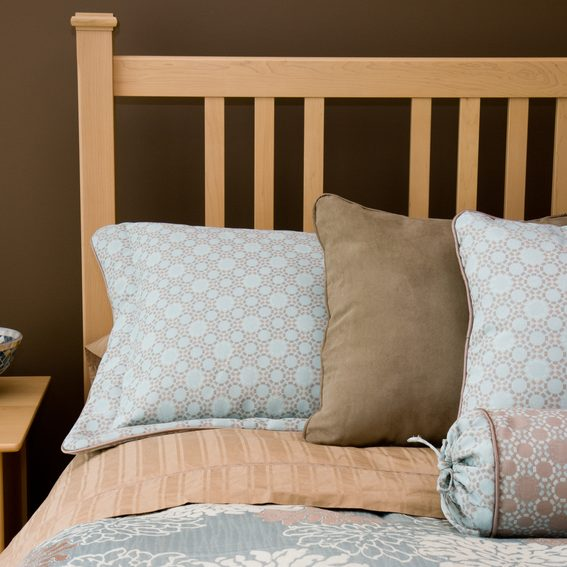 Elegant blue and brown bed pillows and linens in a modern master bedroom.