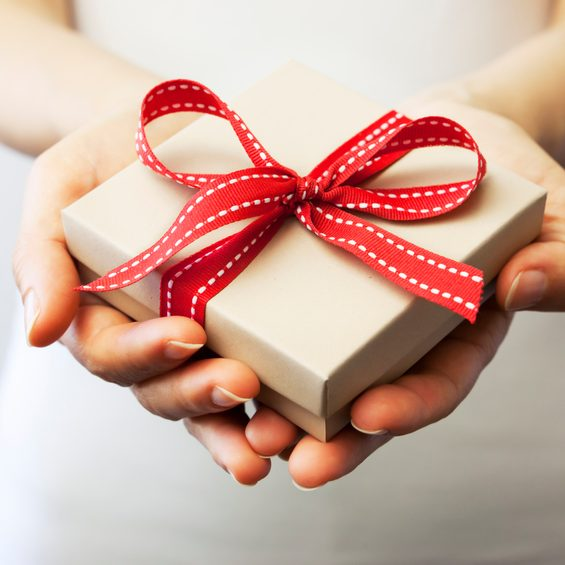 A person holding a gift box. A woman holding a small gift box in a gesture of giving. Christmas holiday or special occasion gift box with red ribbon.