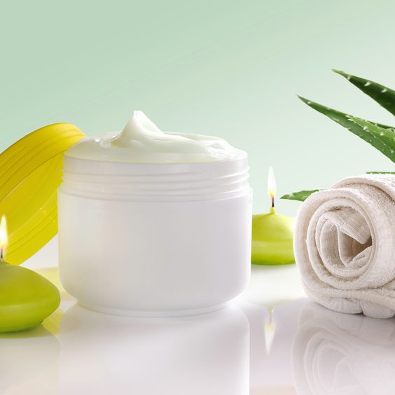 White plastic container with facial or body cream of aloe vera. Candles, towel and plant decoration and green background isolated. Front view